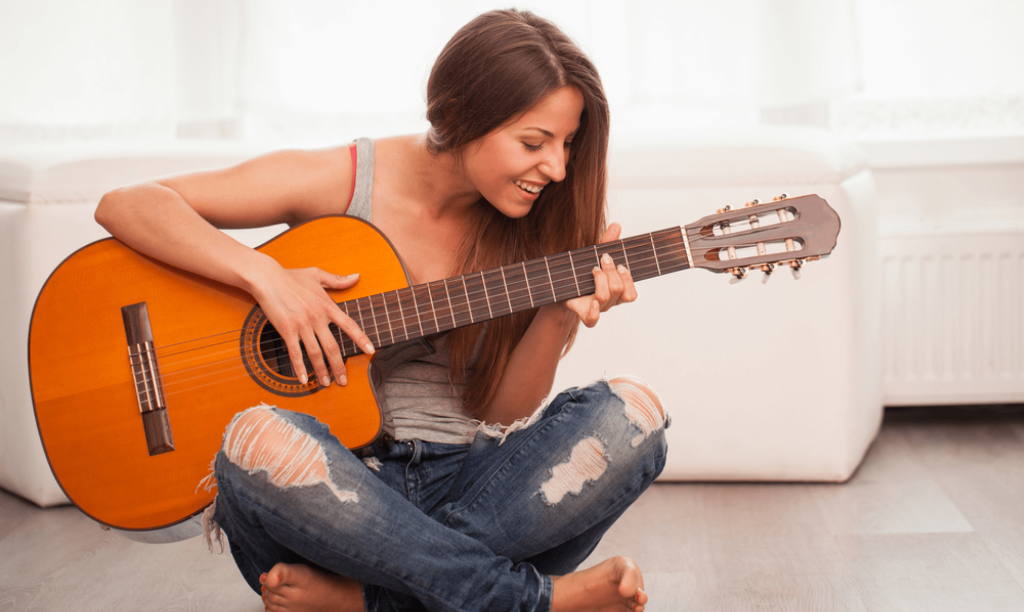 woman smiling while playing guitar